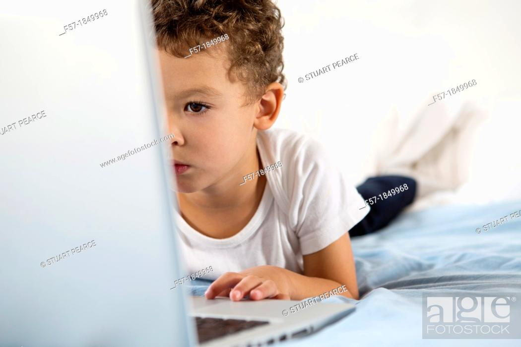 Stock Photo: Four year old boy playing games on a laptop.