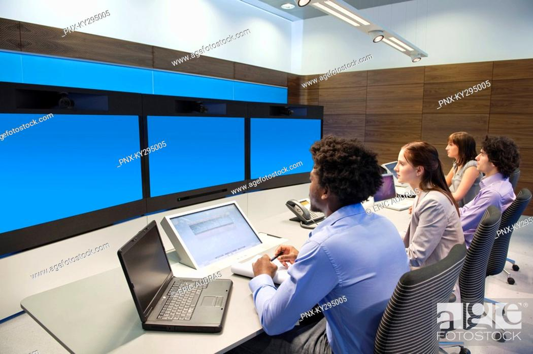 Stock Photo: Business executives working in a control room.