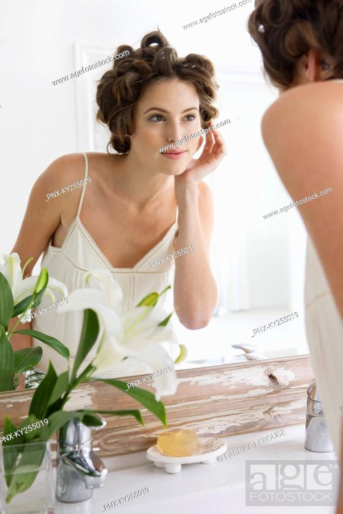 Stock Photo: Woman examining her face in the mirror.
