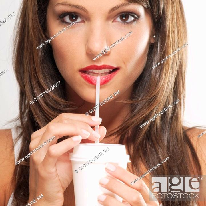 Stock Photo: Portrait of a woman drinking coffee with a straw.