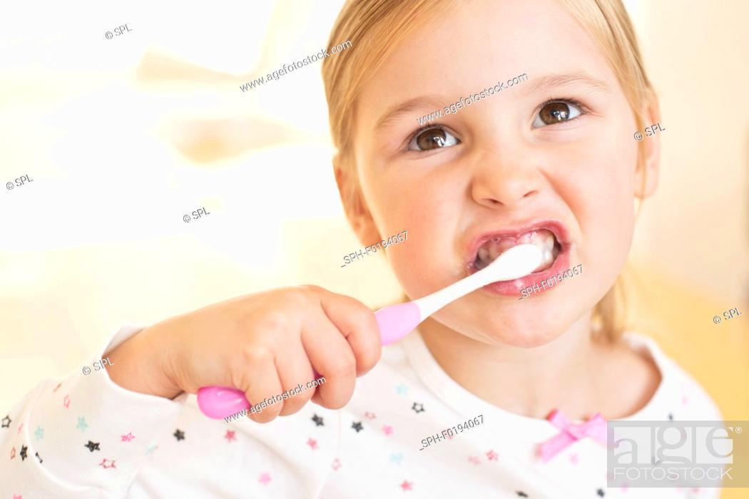 Stock Photo: Young girl brushing teeth.