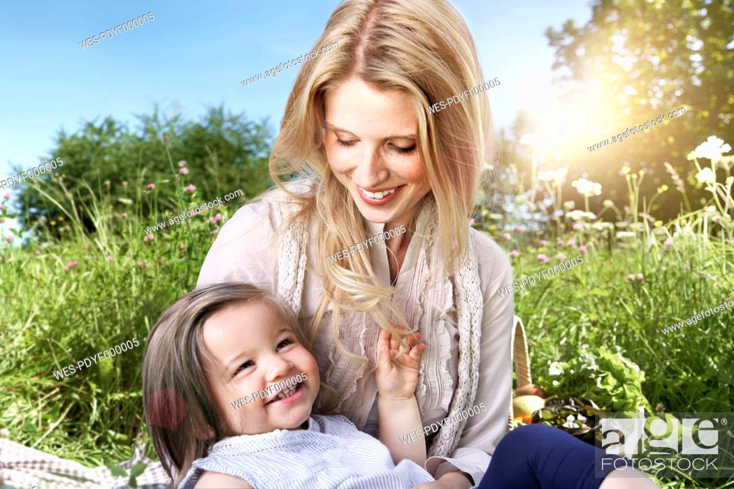 Stock Photo: Germany, Cologne, Mother and daughter sitting on meadow, smiling.