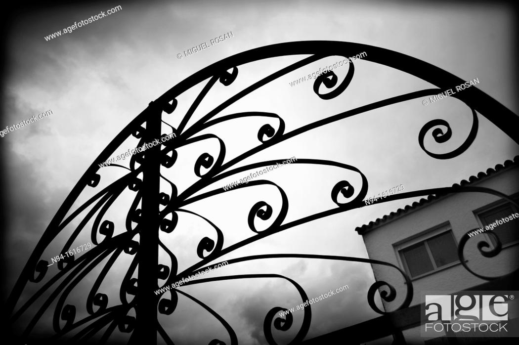 Stock Photo: Top of the iron gate wrought iron and the entrance to a home field.