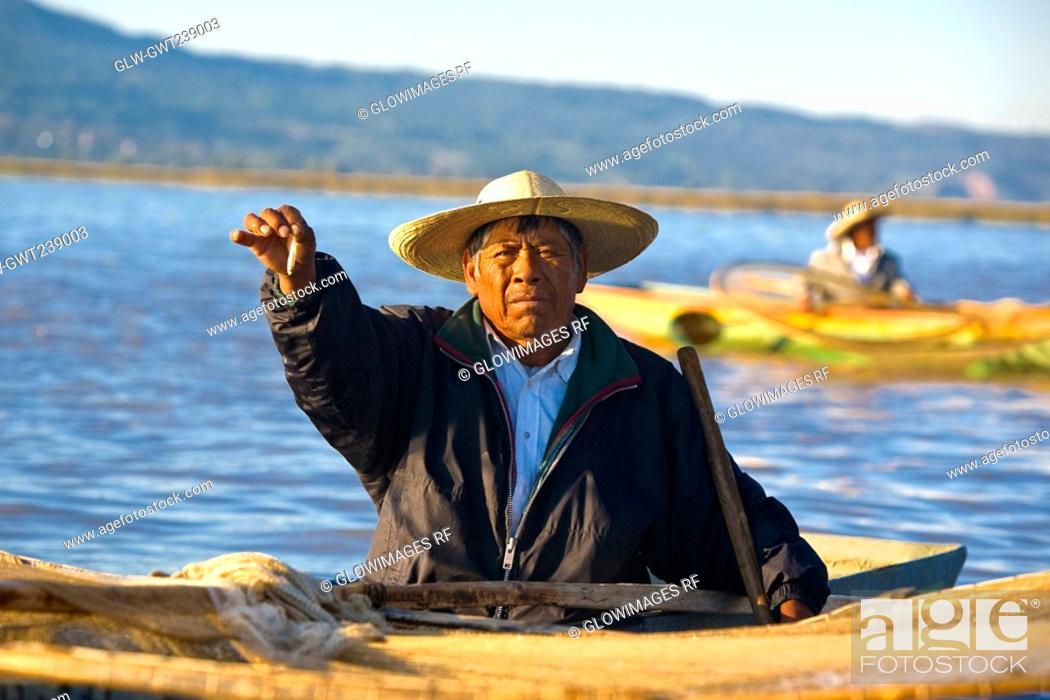 Stock Photo: Fisherman on a boat and showing a fish, Janitzio Island, Lake Patzcuaro, Patzcuaro, Michoacan State, Mexico.