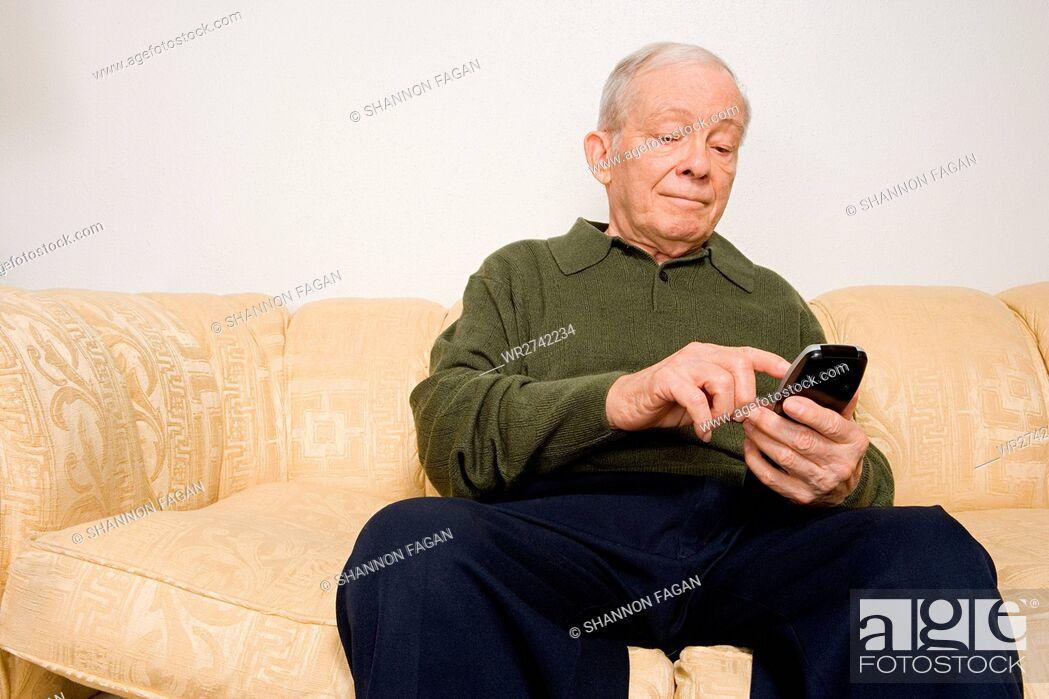 Stock Photo: Elderly man using remote control.