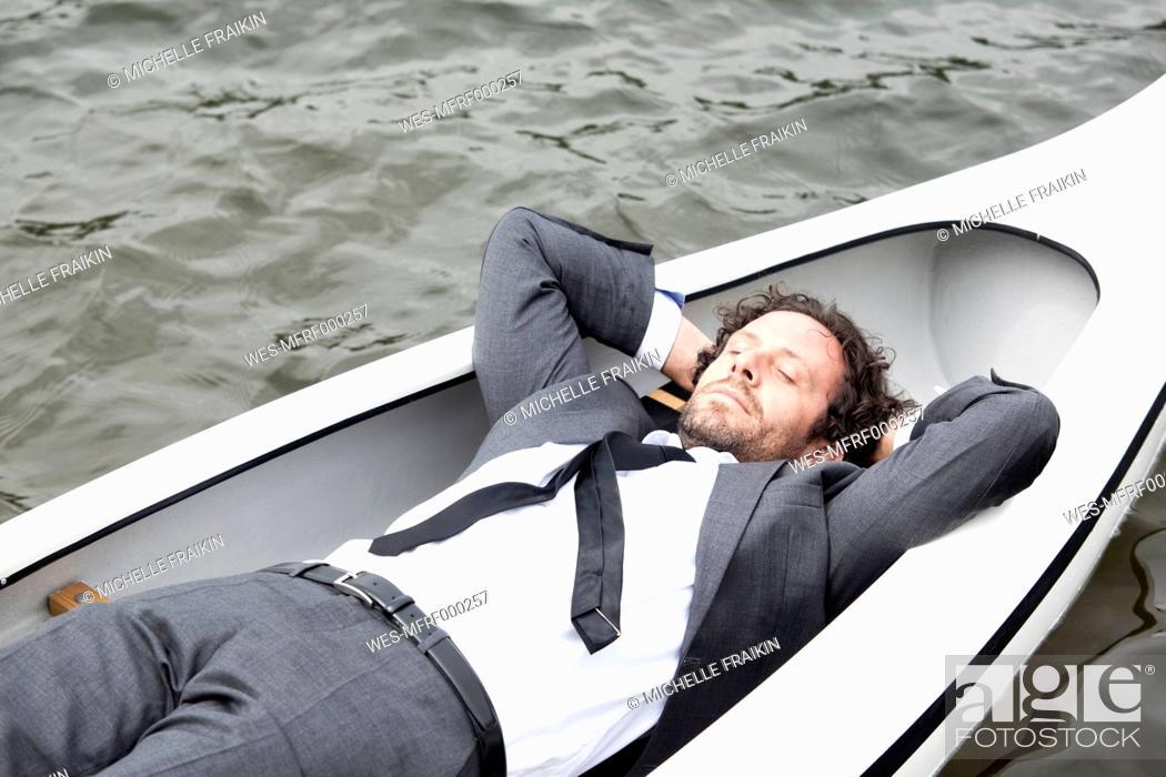 Photo de stock: Germany, Rur Reservoir, businessman sleeping in canoe.