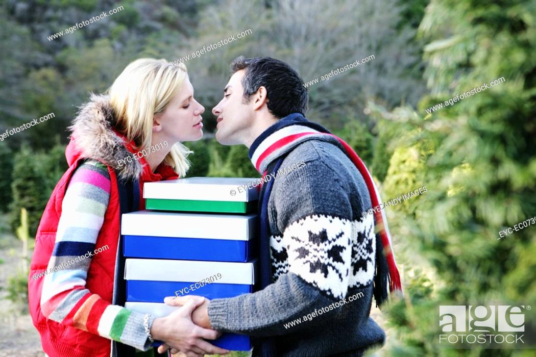 Stock Photo: Couple with Christmas boxes about to kiss.