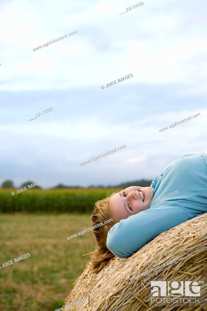 Stock Photo: Teenage girl 16-18 lying on back on bale of hay, smiling, portrait.