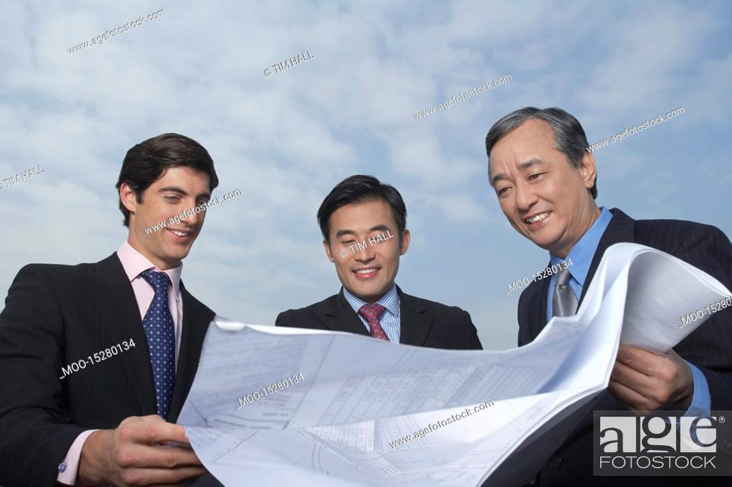 Stock Photo: Three business holding and looking at blueprints smiling.