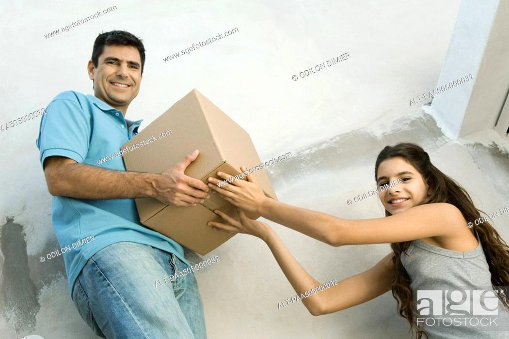 Stock Photo: Father and daughter moving cardboard box together, low angle view.