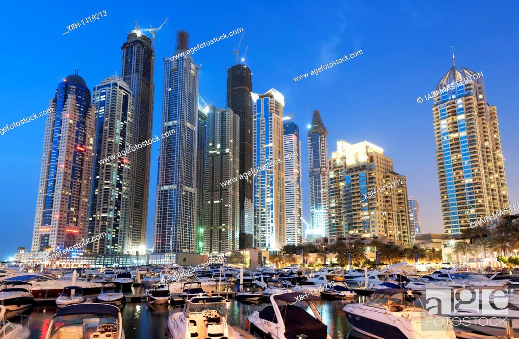 Stock Photo: View of new Dubai Marina with yachts and high rise apartment towers to rear in Dubai United Arab Emirates , UAE.