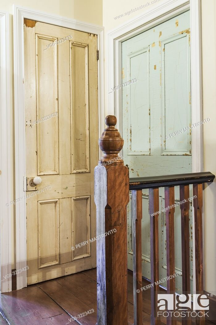 Stock Photo: Wooden newel post and railing next to old faded white paint closet and blue bedroom doors on the upper floor hallway inside an old 1835 fieldstone house.
