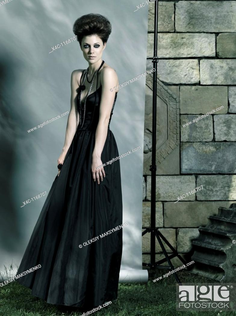 Stock Photo: High fashion photo of a beautiful woman wearing long black dress.