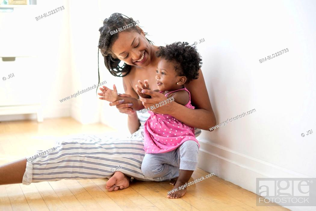 Stock Photo: Black woman sitting on floor kissing clapping hands with baby daughter.