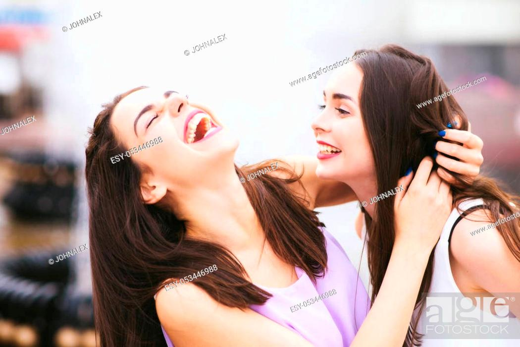 Stock Photo: Two beautiful girlfriends having fun on the street.