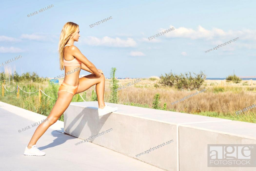 Stock Photo: attractive female athlete stretching legs and exercising, sporty woman doing warm up workout at promenade before training and running.