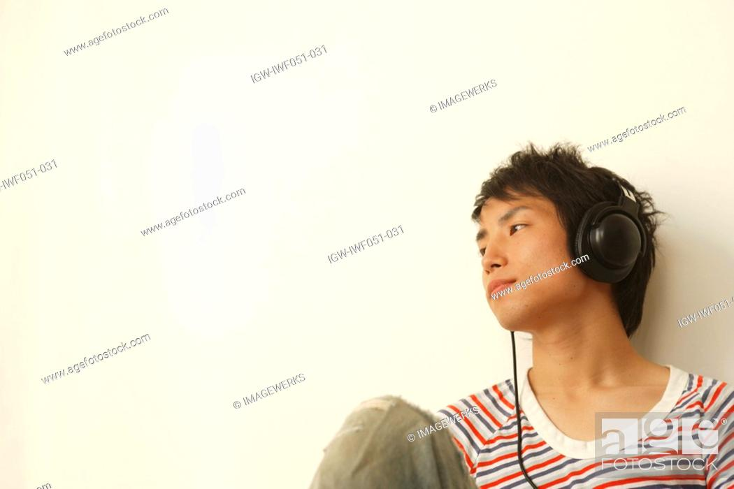 Stock Photo: Young man listening music.
