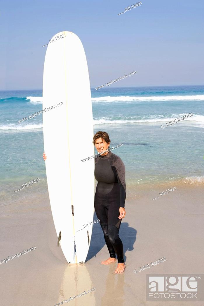 Stock Photo: Female surfer in wetsuit with surfboard on beach, portrait.