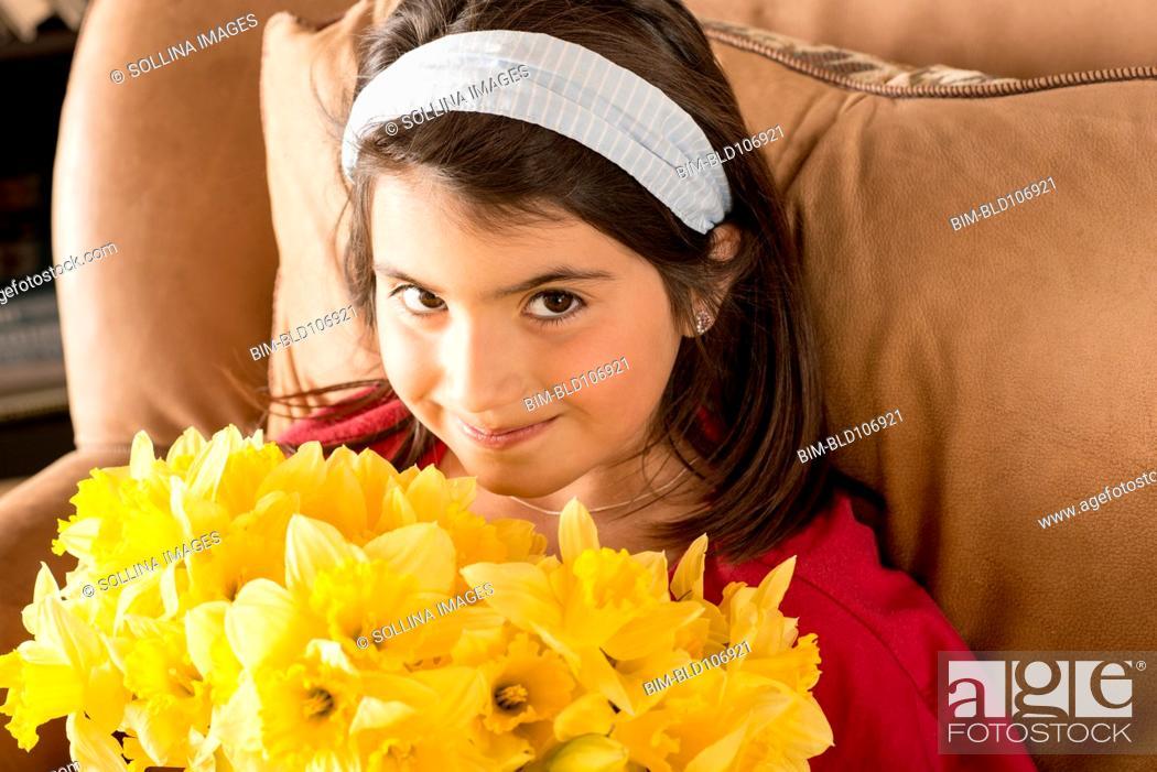 Stock Photo: Hispanic girl holding flowers.
