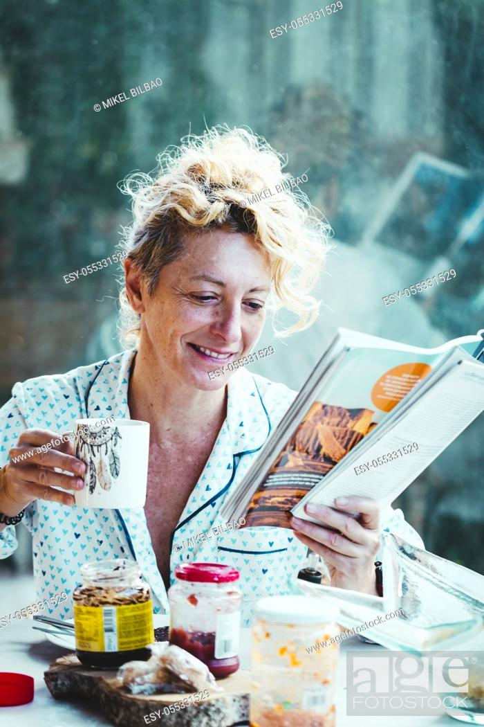 Photo de stock: Blonde young mature woman in pyjamas at home in breakfast time, reading a magazine and having a cup of coffee.