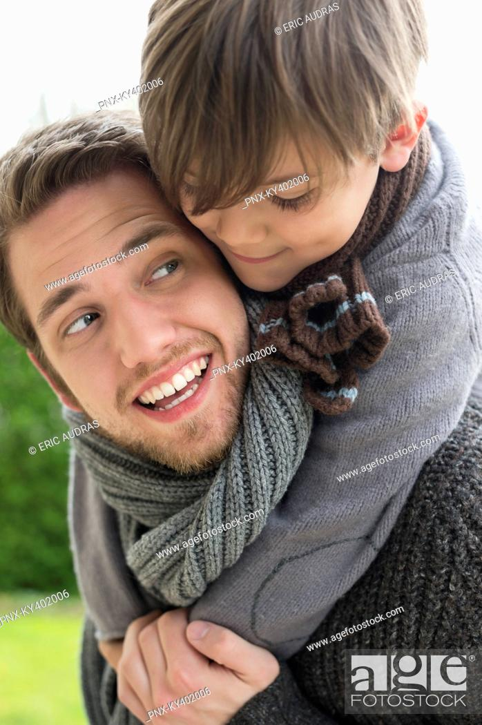Stock Photo: Happy boy riding piggyback on his father.