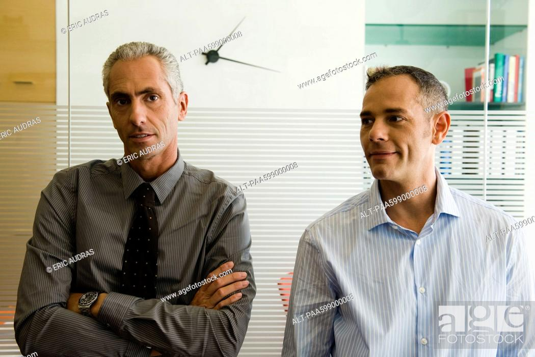 Stock Photo: Businessmen standing side by side in office, portrait.