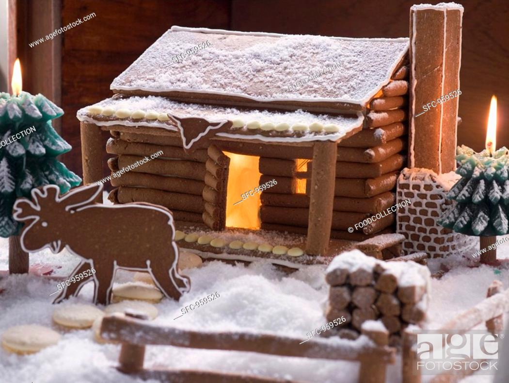 Stock Photo: Gingerbread log cabin in snowy forest with gingerbread elk.