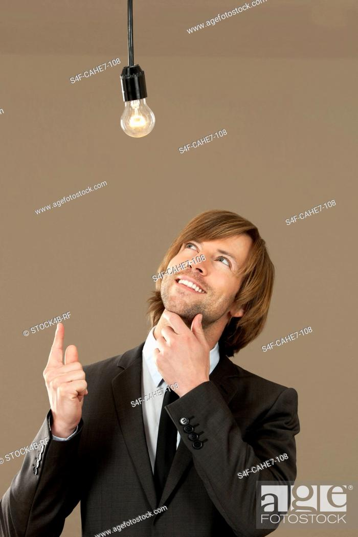 Stock Photo: Businessman wearing suit looking at light bulb.
