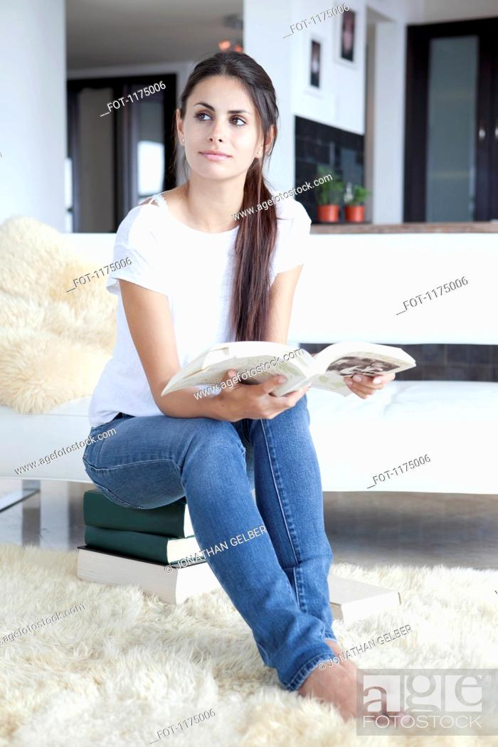 Stock Photo: Woman sitting on books and reading.