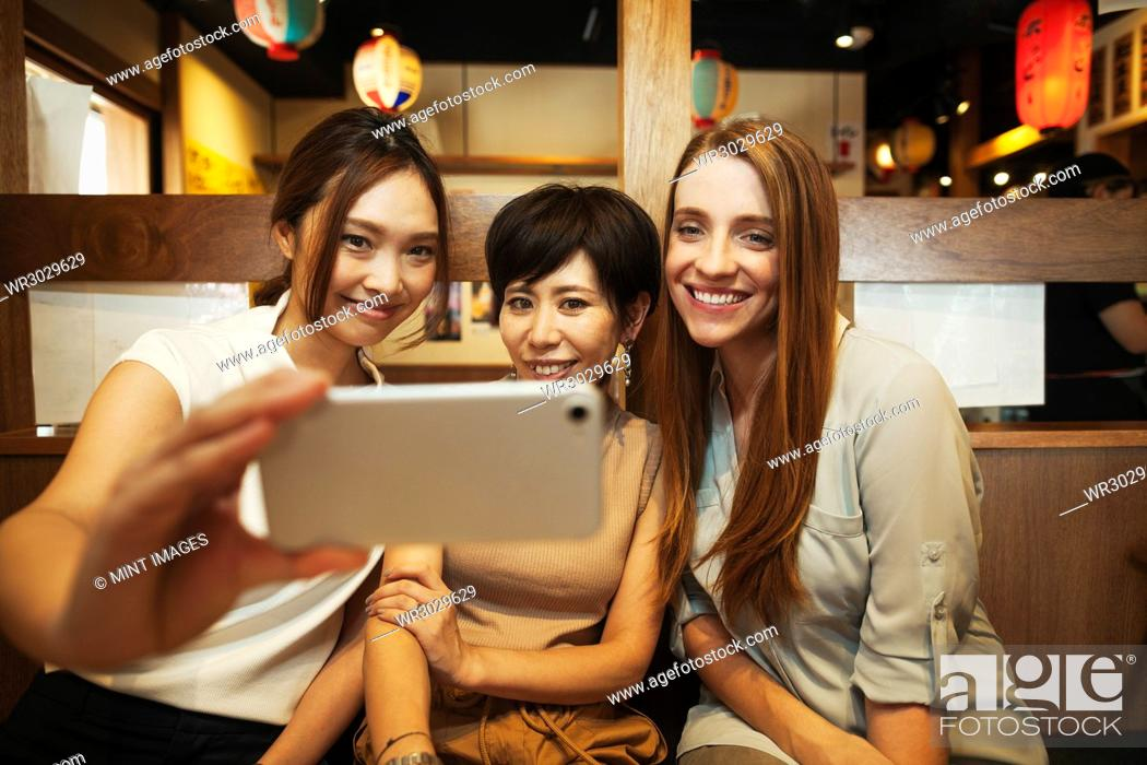 Stock Photo: Three women sitting side by side in a restaurant, taking selfie with smartphone.