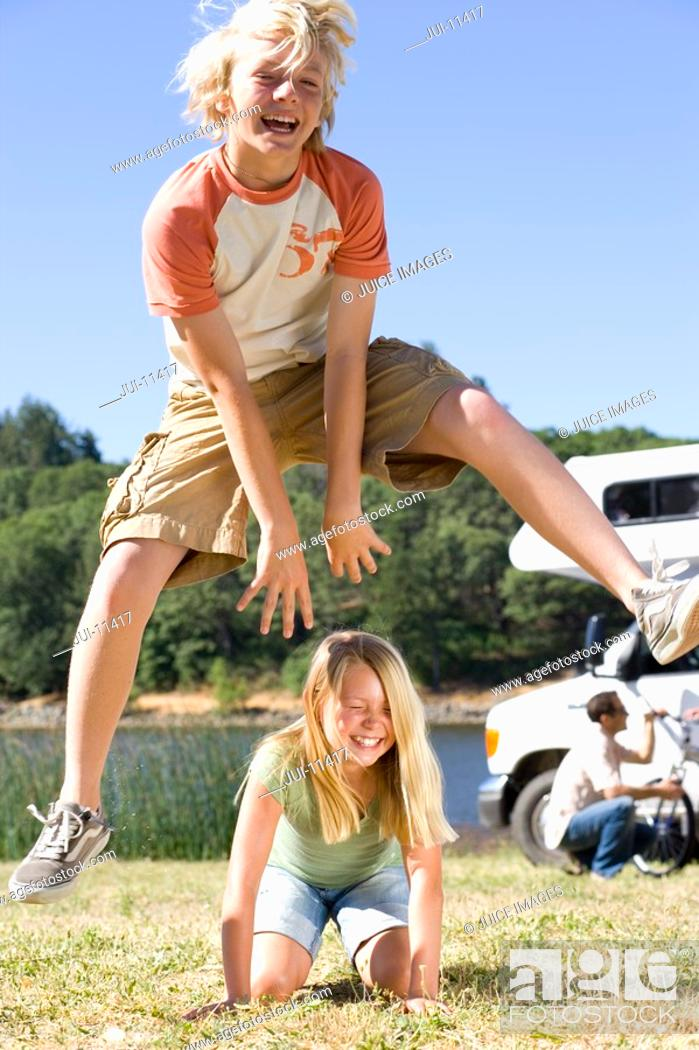 Stock Photo: Boy 10-12 jumpping over sister 9-11 on grass by motor home.