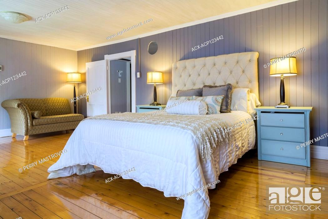 Stock Photo: Queen size bed with white bedspread, beige cloth headboard, light blue end tables with drawers and gold and grey upholstered recamier in master bedroom with.