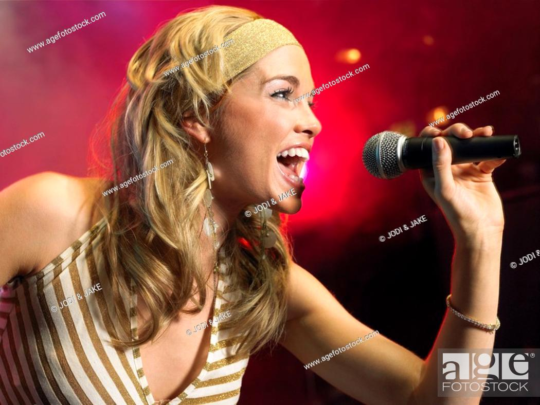 Stock Photo: Young Woman Singing on stage in Concert side view.