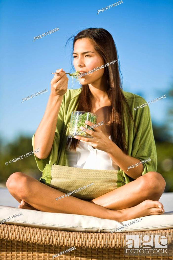 Stock Photo: Woman sitting on a mattress and eating bean sprouts.