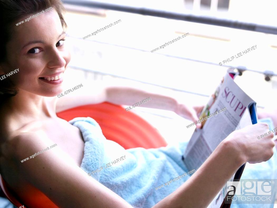 Stock Photo: Woman sitting at window reading.