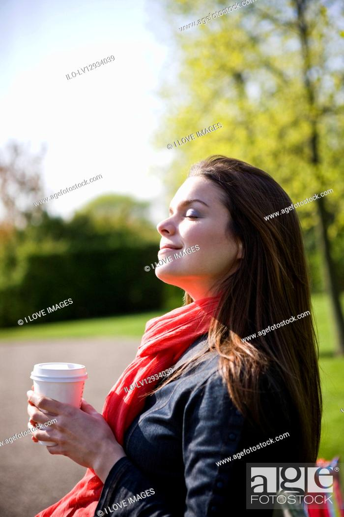 Stock Photo: A young woman enjoying the sun, holding a hot drink.