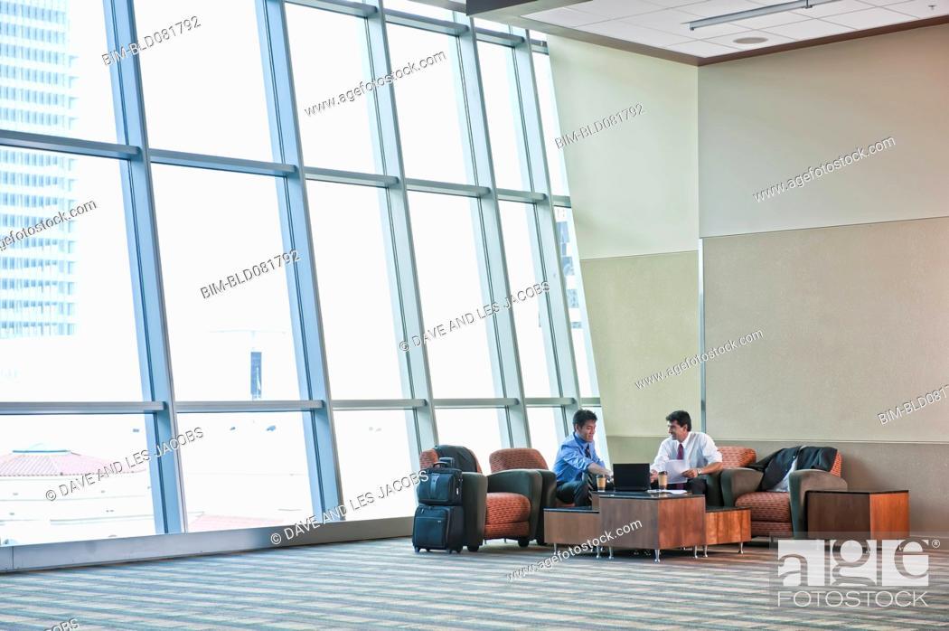 Stock Photo: Traveling businessmen having meeting in lobby.