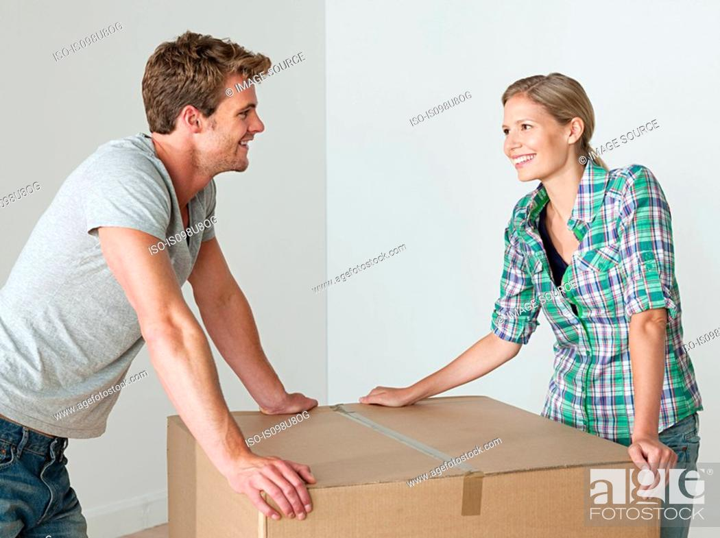 Stock Photo: Young couple with cardboard box.