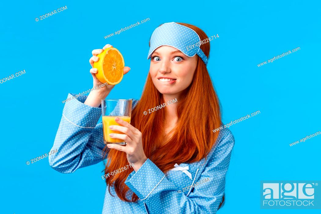 Stock Photo: Excited and cute pretty caucasian redhead woman in pyjama and sleep mask, biting lip tempting and eager try fresh made orange juice.