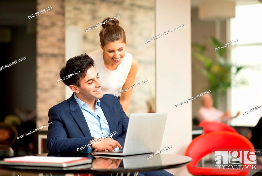 Stock Photo: Businessman and woman looking at laptop in office.