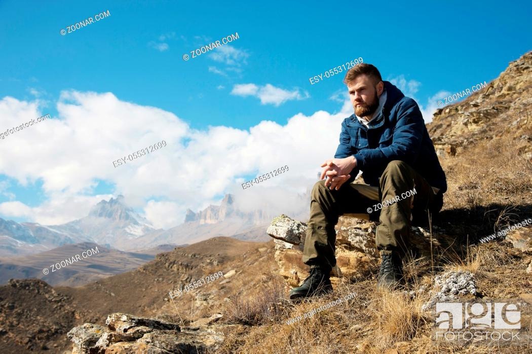 Photo de stock: A portrait of a stylish bearded hipster sitting on a rock against the backdrop of epic rocks and contemplating into the distance thinking about life.