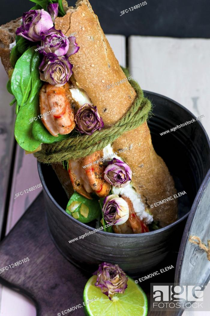 Stock Photo: Baguette sandwich with prawns and dried rose buds.