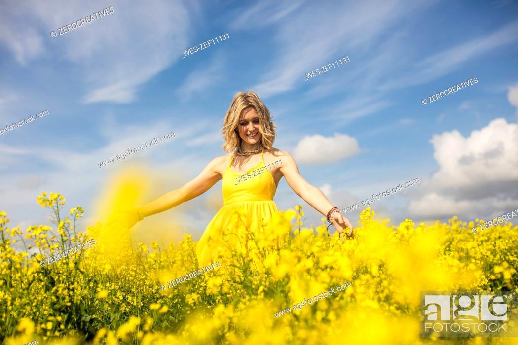 Stock Photo: Happy blond woman wearing yellow dress standing in rape field.