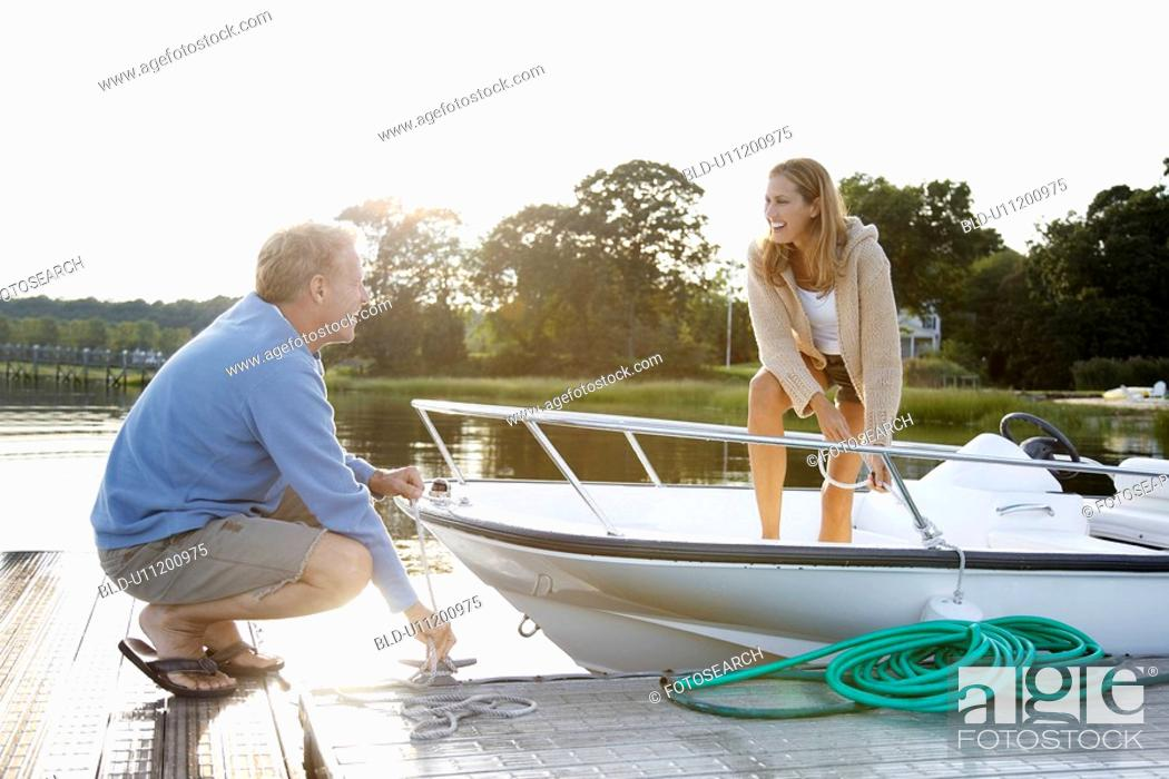 Stock Photo: Couple untying motorboat from dock.