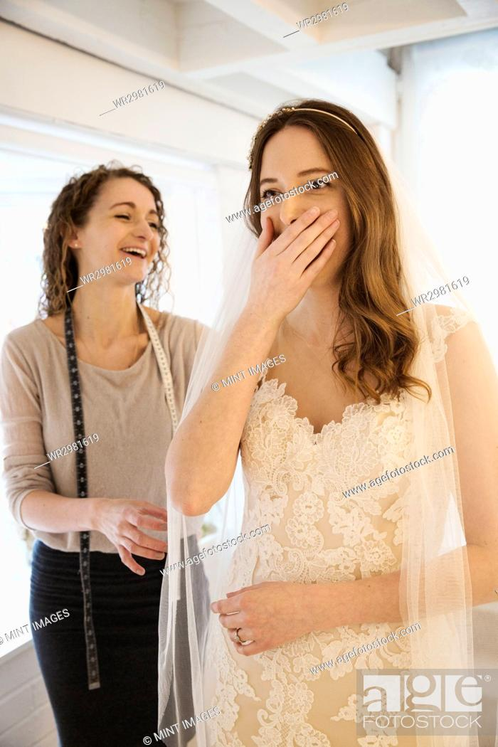 Stock Photo: A young woman trying on a wedding dress, with lace overlay on the bodice and skirt, her hand covering her mouth, expressing surprise and delight.