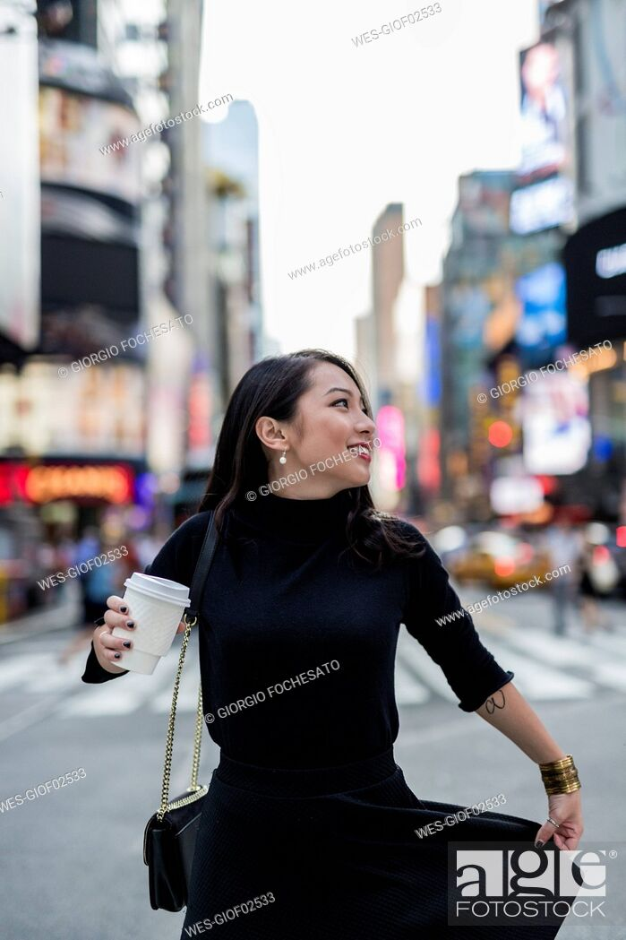 Photo de stock: USA, New York City, Manhattan, young woman dressed in black with coffee to go on the street.
