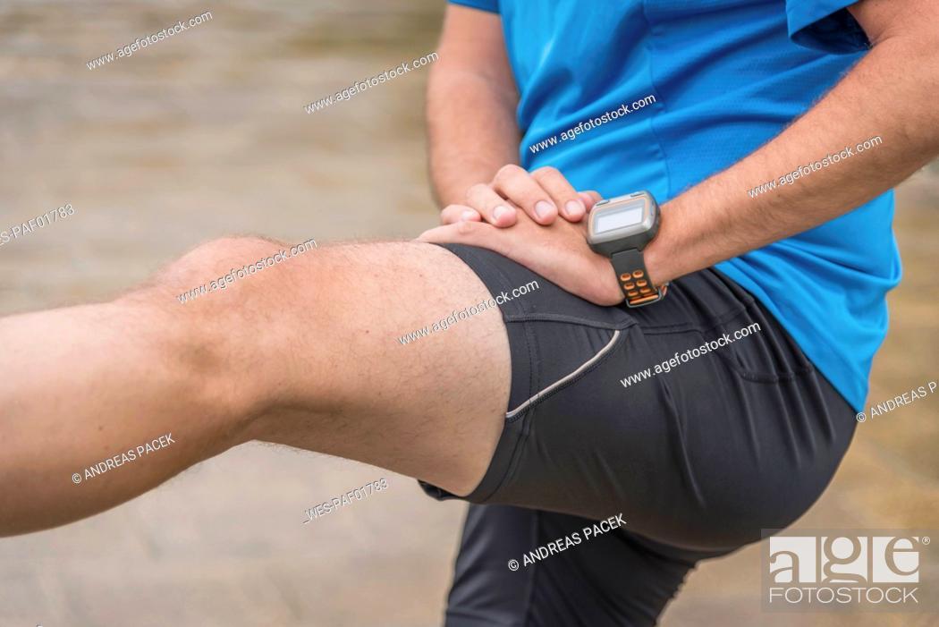 Photo de stock: Man stretching leg, wearing a smartwatch.