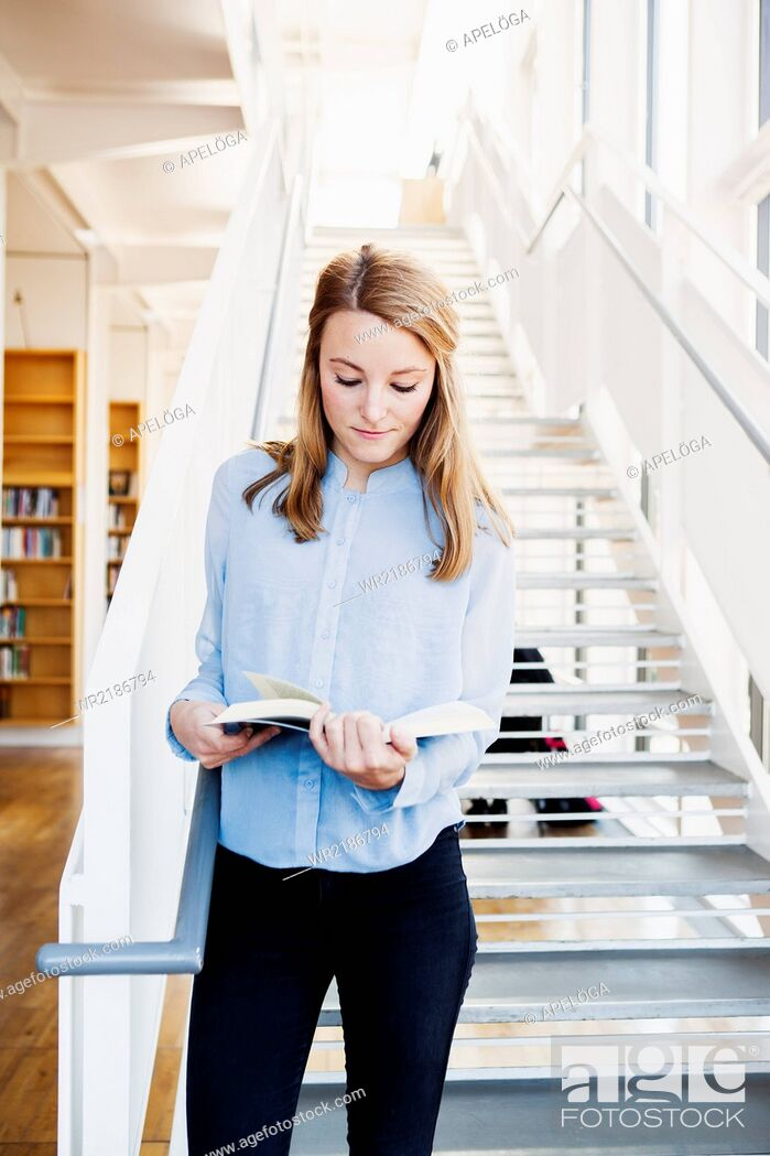 Stock Photo: Young woman reading book while standing on steps in library.