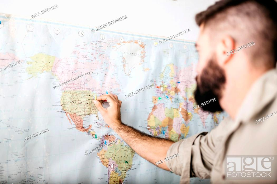 Stock Photo: Young man selecting travel destinations on a world map.
