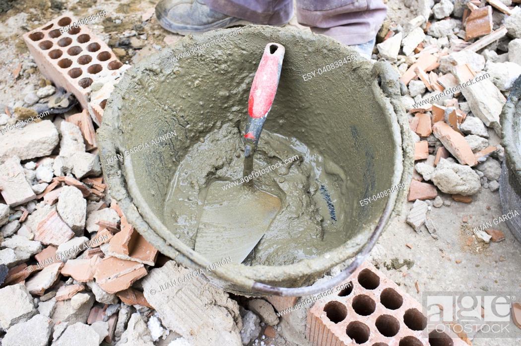 Imagen: Empty plaster bucket over brick rubble. Overhead shot.